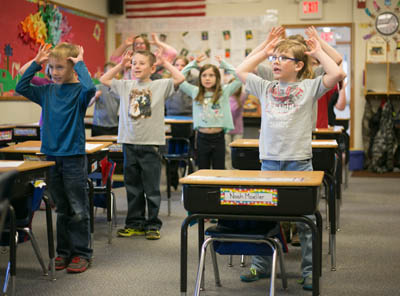 Students singing in a classroom with their hands in the air