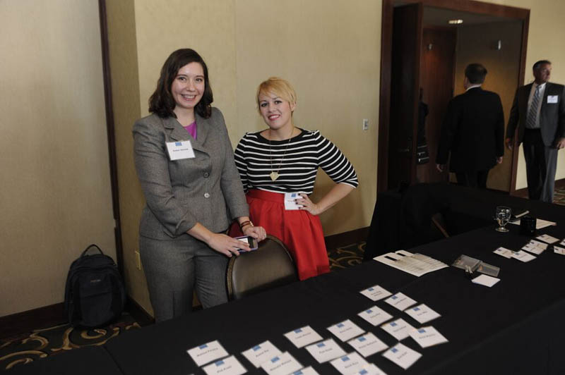 Amber DeLind and Hailey Zureich of The Center for Michigan, standing behind a registration table