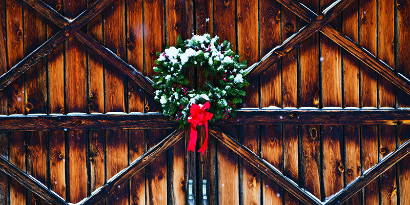 A Christmas wreath in the middle of a weathered barn door