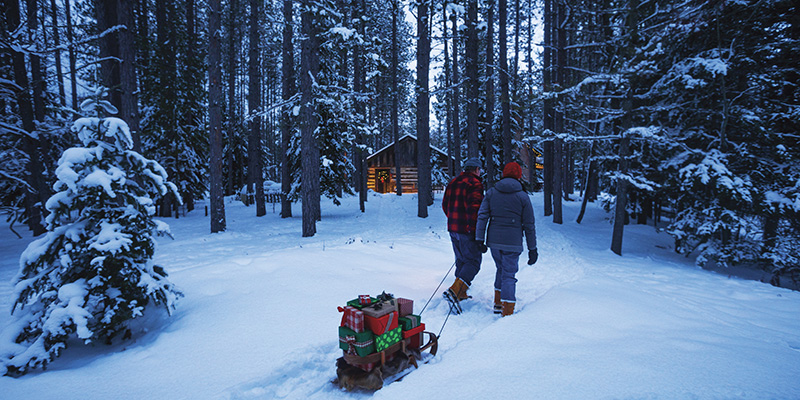 John and Sue Paul of Traverse City pulling a sled filled with gifts through a pine forest near Grayling. (Courtesy photo, Cabela's)