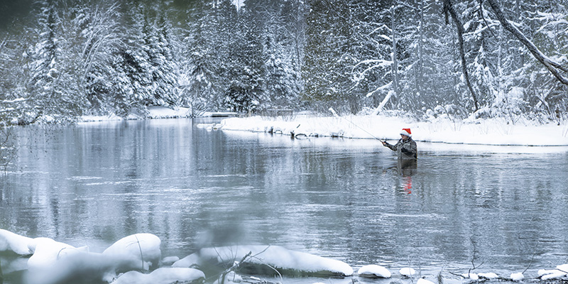 A man in a Santa hat fly fishing in the middle of the river, with snowy landscape surrounding it