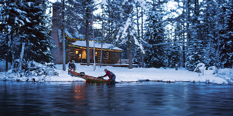 Two men taking a boat out onto the water in front of a cabin lit with interior and holiday lights