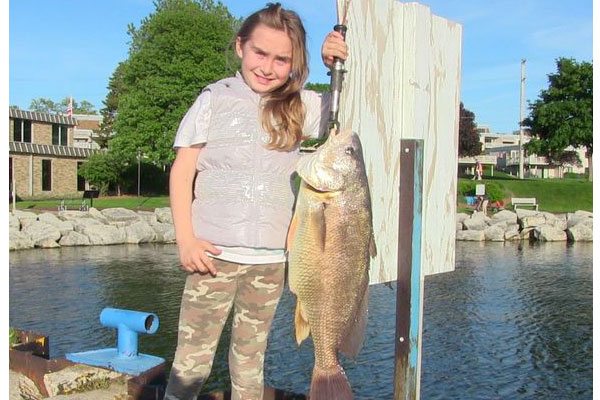 Sasha Wheeler on a boat holding up a caught freshwater drum fish