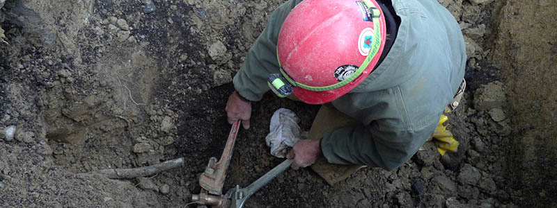 Plumber Ken Davison performing wrench work inside an excavated hole