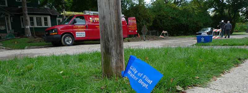 A City of Flint Water Dept. flag in the ground near a utility pole