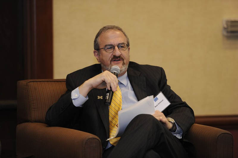Dr. Mark Schlissel, speaking into a microphone from a lounge chair