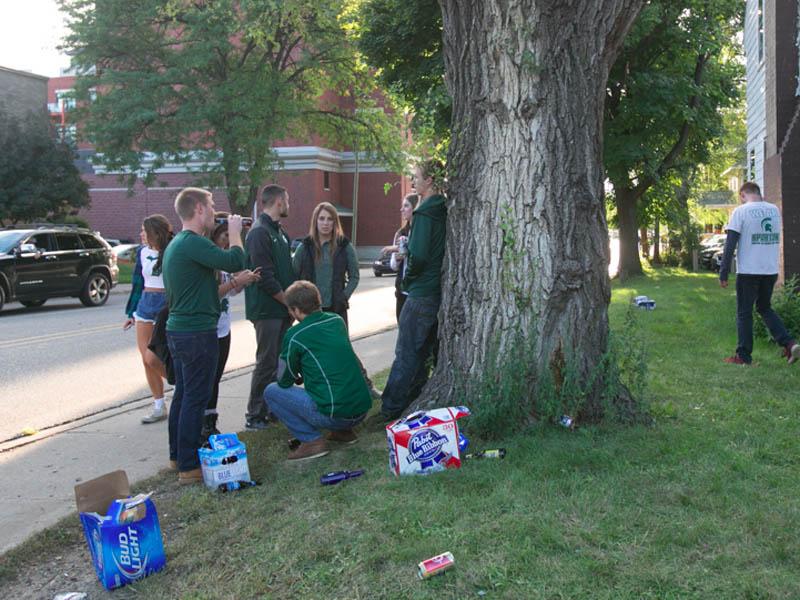 MSU students drinking under a tree