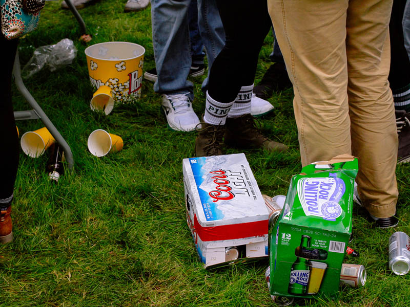 Discarded beer, cups, and popcorn containers in the grass