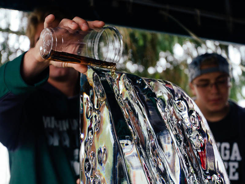 A drink being poured down an ice luge