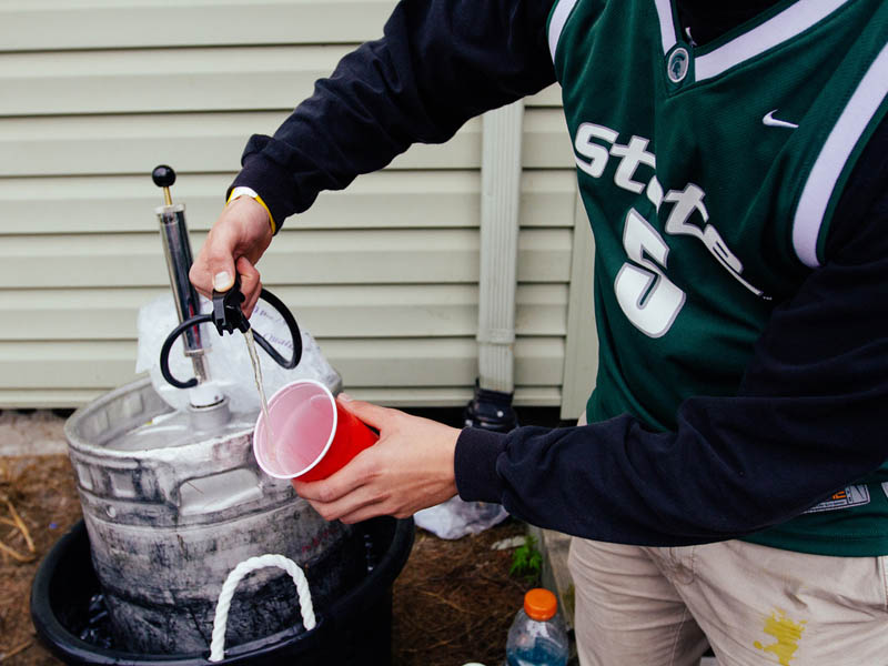 An MSU student pouring beer from a keg