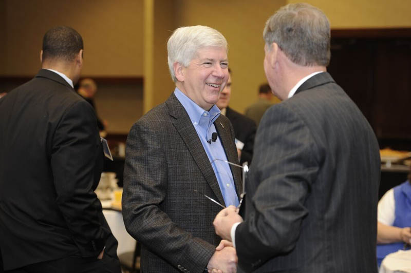 Governor Rick Snyder smiling while shaking a man's hand