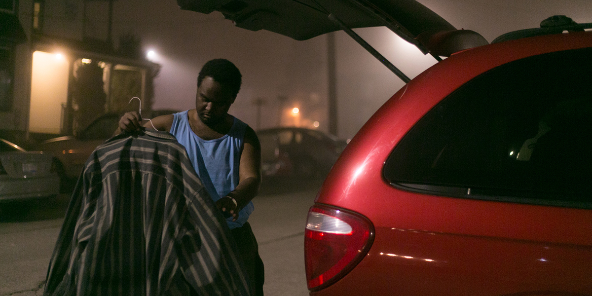 Ramone Williams, standing in front of his minivan's trunk, hanging a dress shirt on a hanger