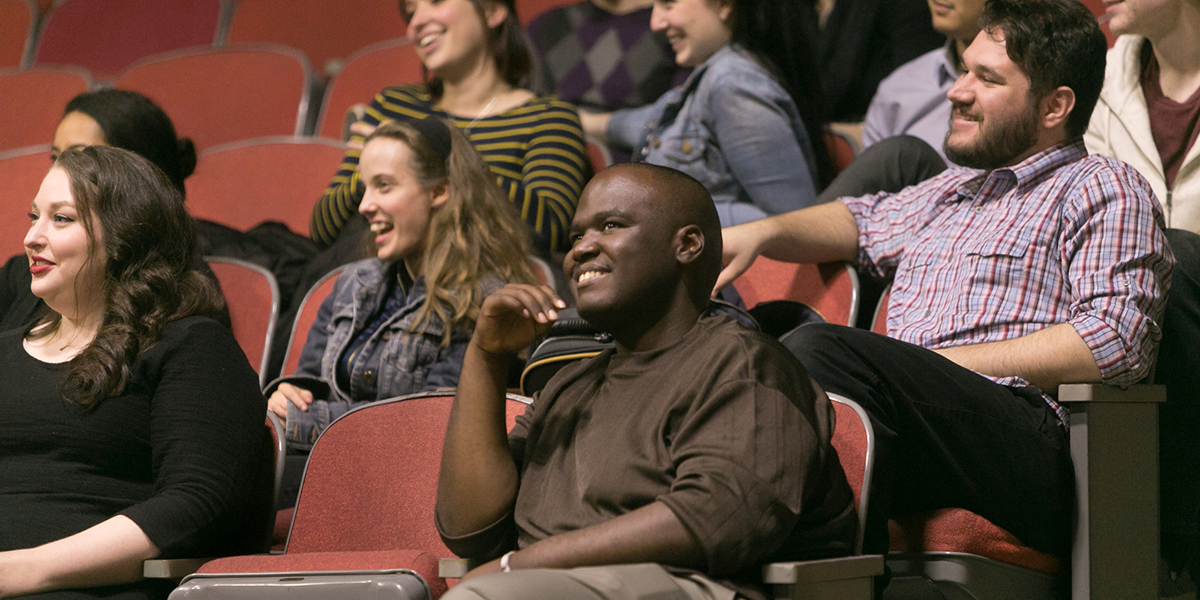 Ramone Williams smiling while seated in the audience for a Shakespeare monologue class