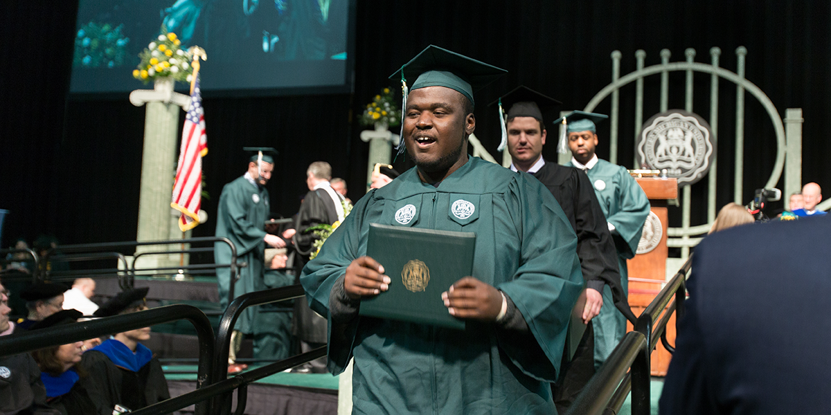 Ramone Williams smiling as he leaves the graduation stage with his diploma
