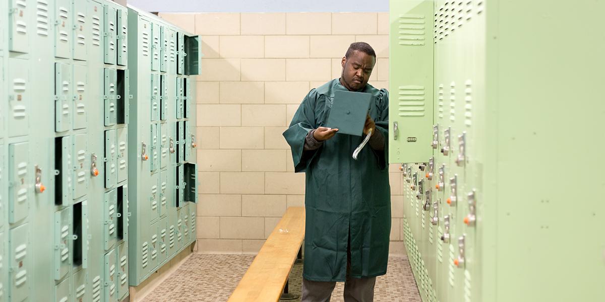 Ramone Williams examining his graduation cap in a locker room
