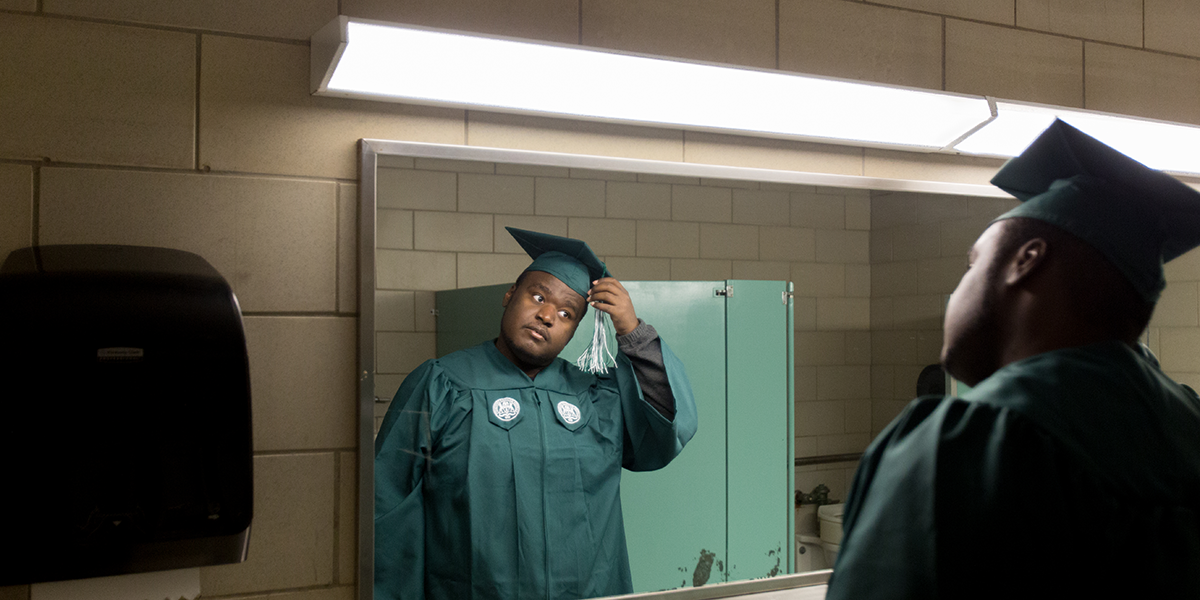 Ramone Williams adjusting his graduation cap tassel in the bathroom mirror