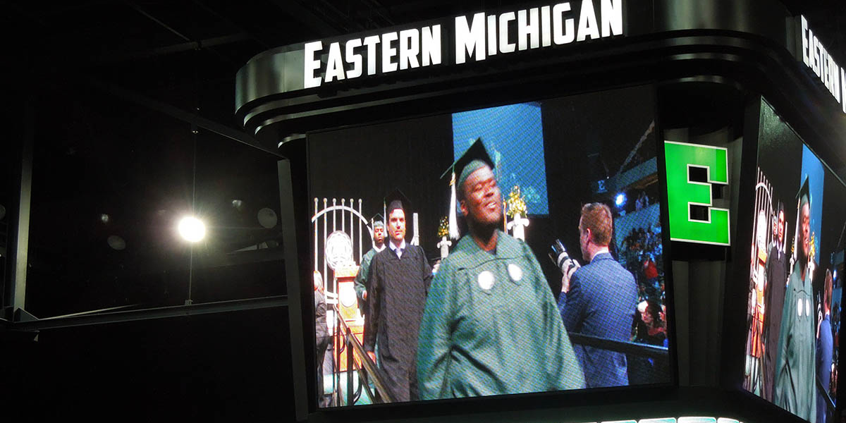 Ramone Williams leaving the stage after receiving his diploma, as displayed on the EMU scoreboard