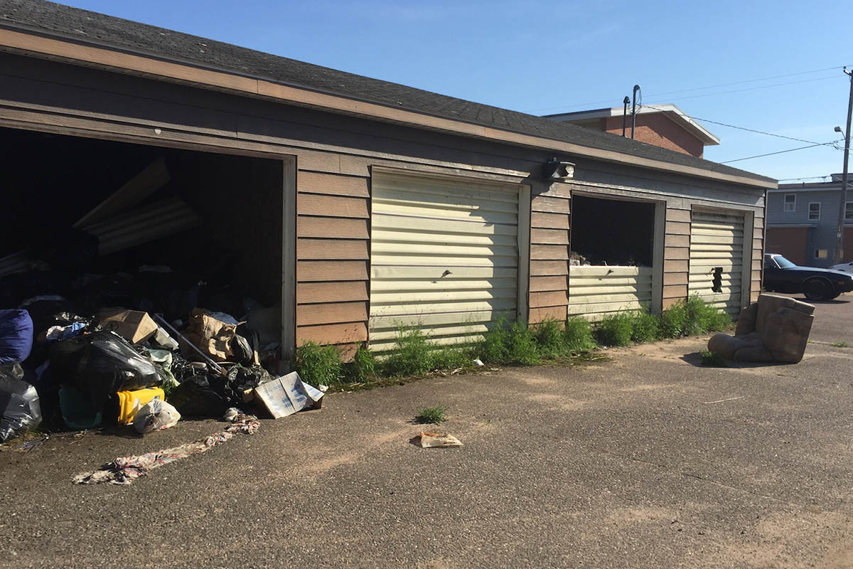Trash spilling out of run-down garages