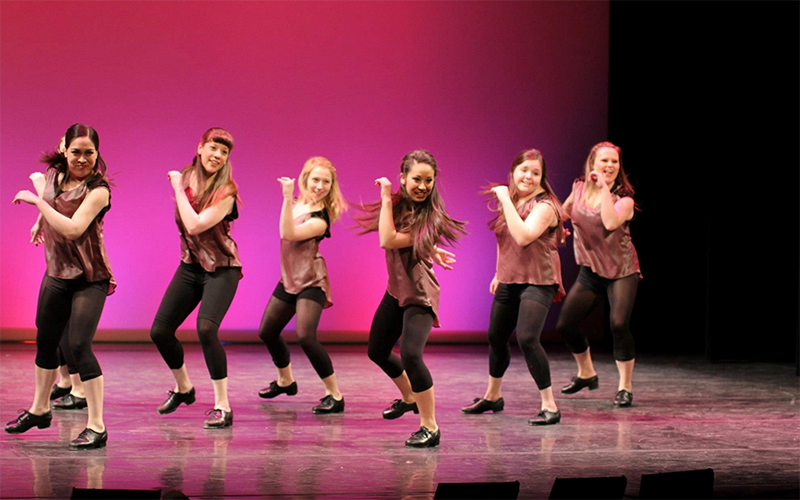 Six tap dancers performing on a stage