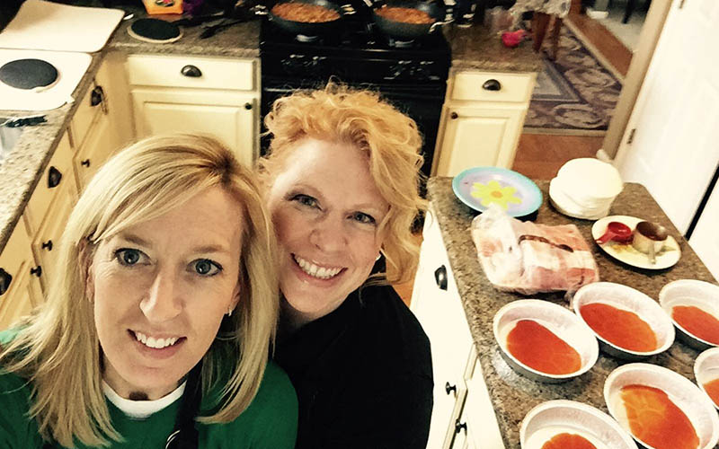 Erinn Smiley-Studier and Monica Spiers taking a selfie with food on an island behind them