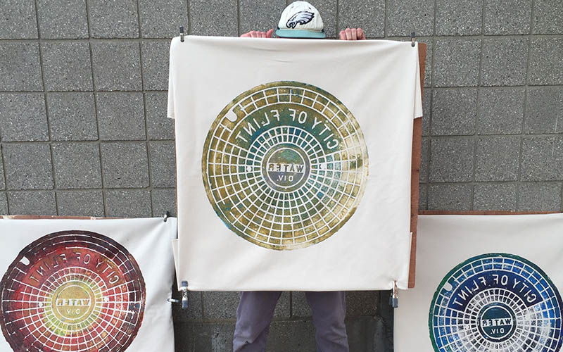 Russell Muits holding up a manhole cover print, with another on each side of him on the ground