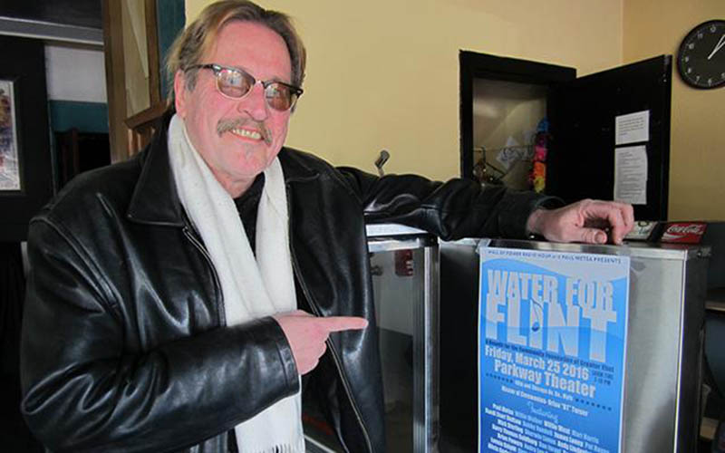 Paul Metsa pointing at a poster for a Water For Flint benefit