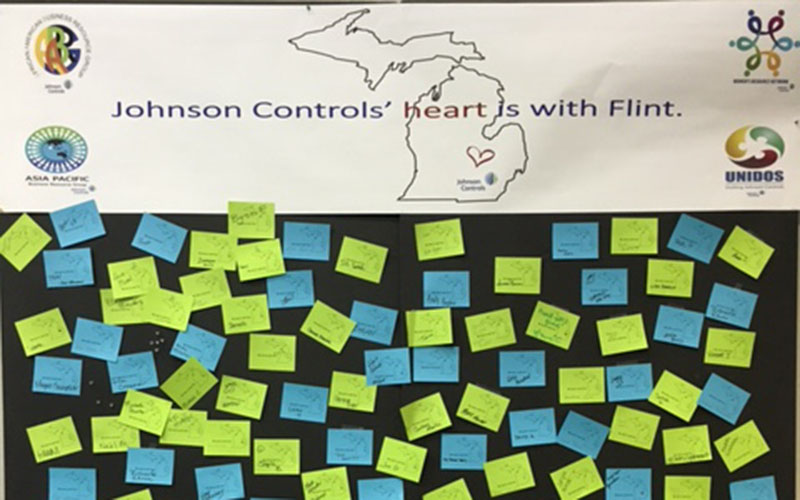 "Sticky notes on a bulletin board with a banner saying ""Johnson Controls' heart is with Flint"""