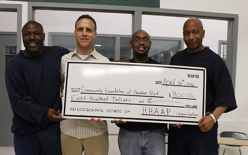 Four men standing in a prison room with an oversized $800 check made out to the Community Foundation of Greater Flint