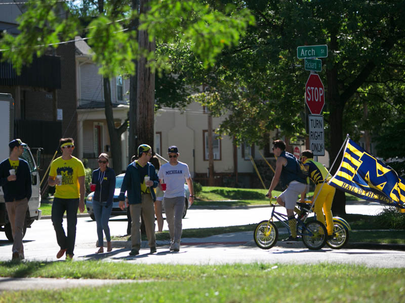 U of M students walking and bicycling near an intersection
