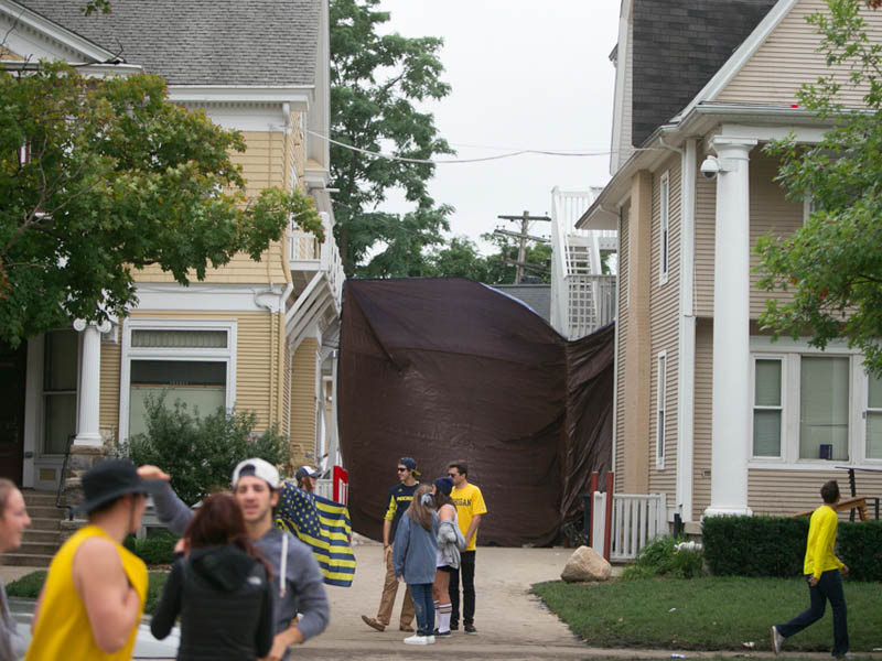 A tarp hung between two houses in the background of a group of students