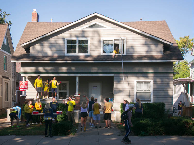 Students in a yard as a beer funnel is extended from the second-floor window