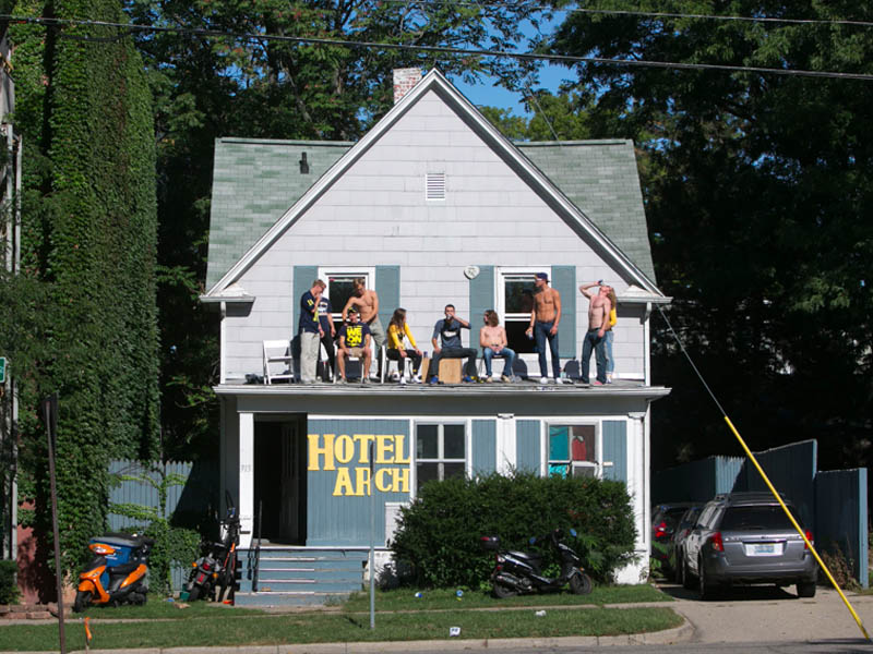 U of M fans standing on the roof of a building labeled Hotel Arch
