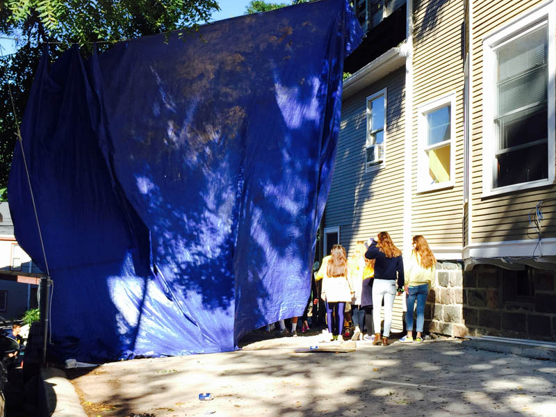A large blue tarp hung next to a house, hiding the alley from view