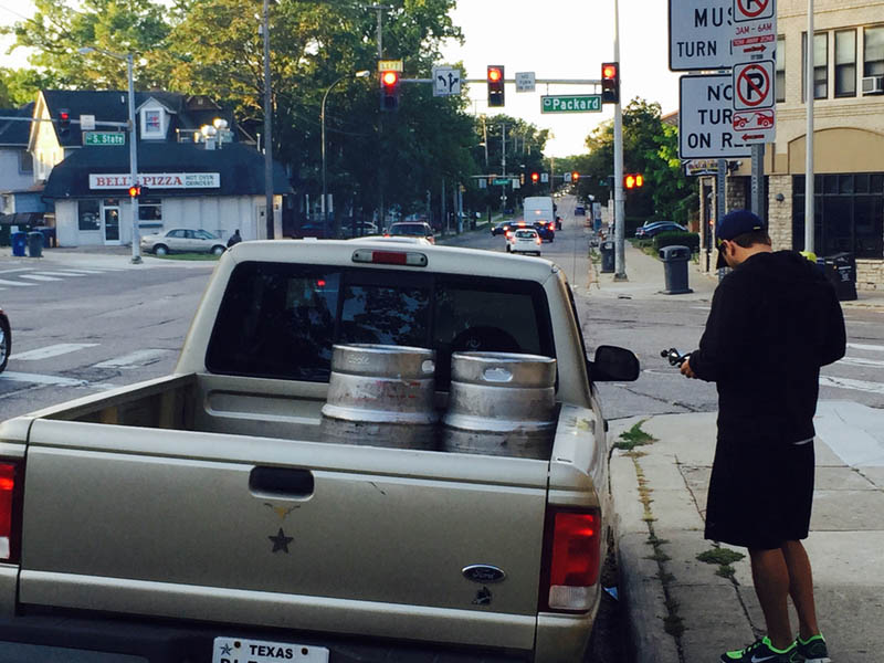 A truck parked on a corner with two beer cans in the cargo bed