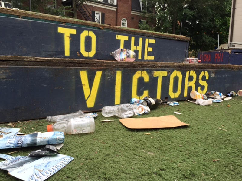 """A """"To The Victors"""" platform in a yard, surrounded by trash"""