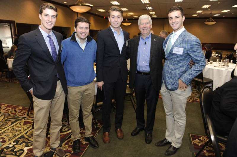 Governor Rick Snyder with several college students at a formal event