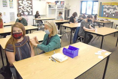 Annelle Kastor, a public health nurse with the Grand Traverse County Health Department, administers a Covid-19 vaccine to Alexis Sattler, 16, at Kingsley High School Thursday
