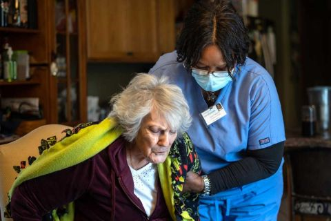 Excellacare Care Provider Sarah Sutherlin helps her client Carmela Palamara, 92, of Brownstown stand up to stretch her legs after the two color and play a game of UNO at Palamara's home on Wednesday, April 14, 2021.