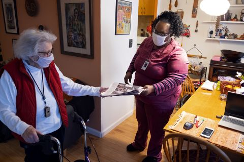 Home health aide hands newspaper to older adult at home