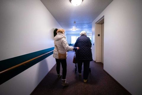 Caregiver helps woman down a hallway