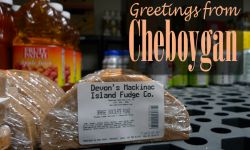 "A postcard that says ""Greetings From Cheboygan"" with a picture of Mackinac Island fudge"