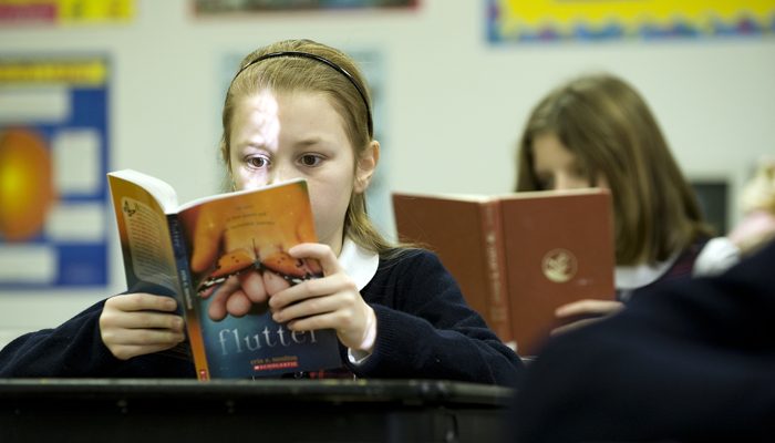 Students reading books at their desks in a classroom